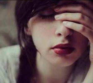 Mujer llevándose la mano a los ojos, reflexionando o sufriendo