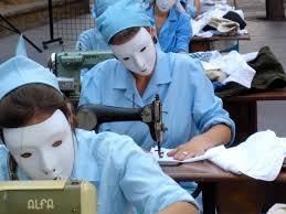 Fábrica con mujeres con uniforme azul cosiendo ante máquinas de coser. Todas llevan caretas blancas
