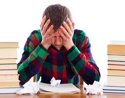 Joven con las manos en la cara ante papeles arrugados con dos pilas de libros a los lados en actitud de fracaso