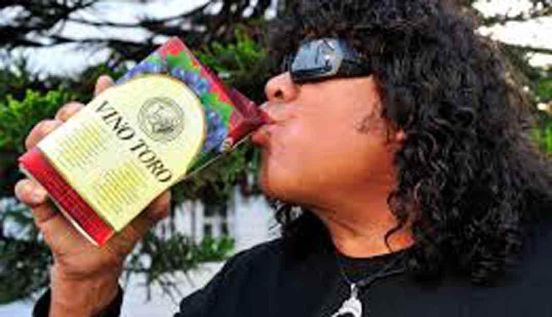 Hombre con gafas oscuras y pelo largo rizado, gordo, de raza gitana, bebiendo a morro en tetrabrik un cartón de vino que pone vino toro