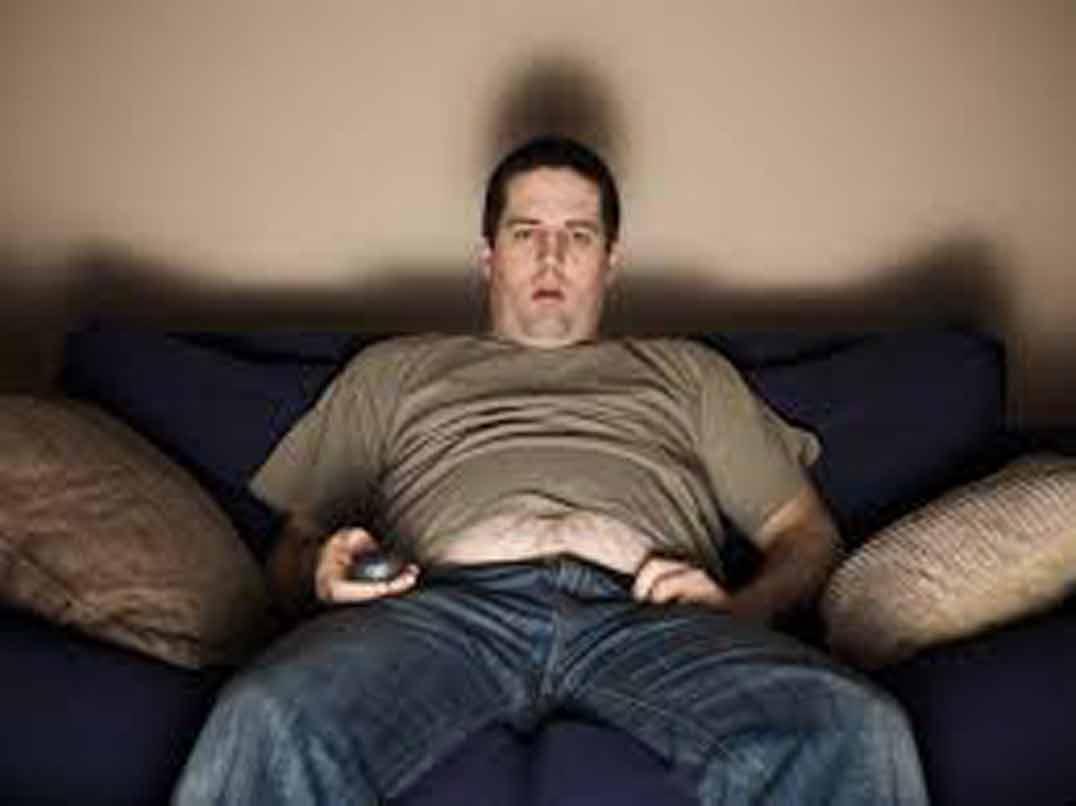 Gordo viendo la tele, con mando en la mano y cara de tonto