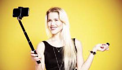 Imagen de una rubia sobre fondo amarillo haciéndose fotos con un móvil y un palo seflie para el artículo la vida es un palo selfie del blog literario lluvia en el mar