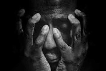 Foto en blanco y negro de hombre con las manos en la cara, tapandola casi entera