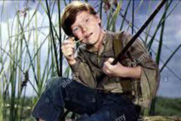 fotograma de película de los años 50 sobre Huckeberry Finn, niño protagonista fumando pipa y con una caña, color