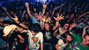 Tumulto de gente de juerga en discoteca, con las manos en alto