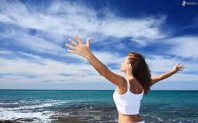 mujer con body blanco abriendo los brazos desde acantilado hacia el mar