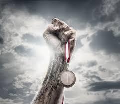 puño y brazo en alto empuñando medalla y fondo de nubes grises, imagen de aire triunfal