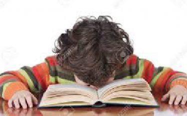muchacho cansado de estudiar, con la cabeza en el libro