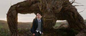 fotograma de la película Un monstruo viene a veme, niño y monstruo árbol detrás