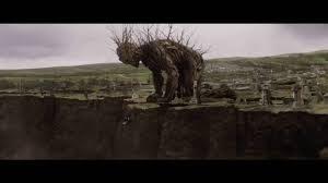 """Fotograma de la película """"un monstruo viene a verme"""" donde se ve al monstruo asomándose al abismo para crítica del blog literario lluvia en el mar"""