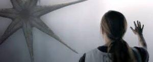 """Película """"La llegada"""", protagonista mirando al extraterrestre que posa una pata en un cristal"""