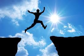 éxito o fracaso, Silueta de hombre saltando sobre un precipicio, de una parte a otra, también en silueta, sobre fondo de cielo azul y sol en contraluz