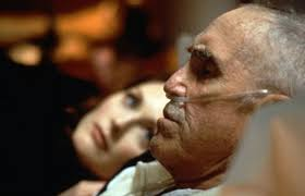 Hombre mayor con sonda en la nariz tumbado y mujer rmirándole