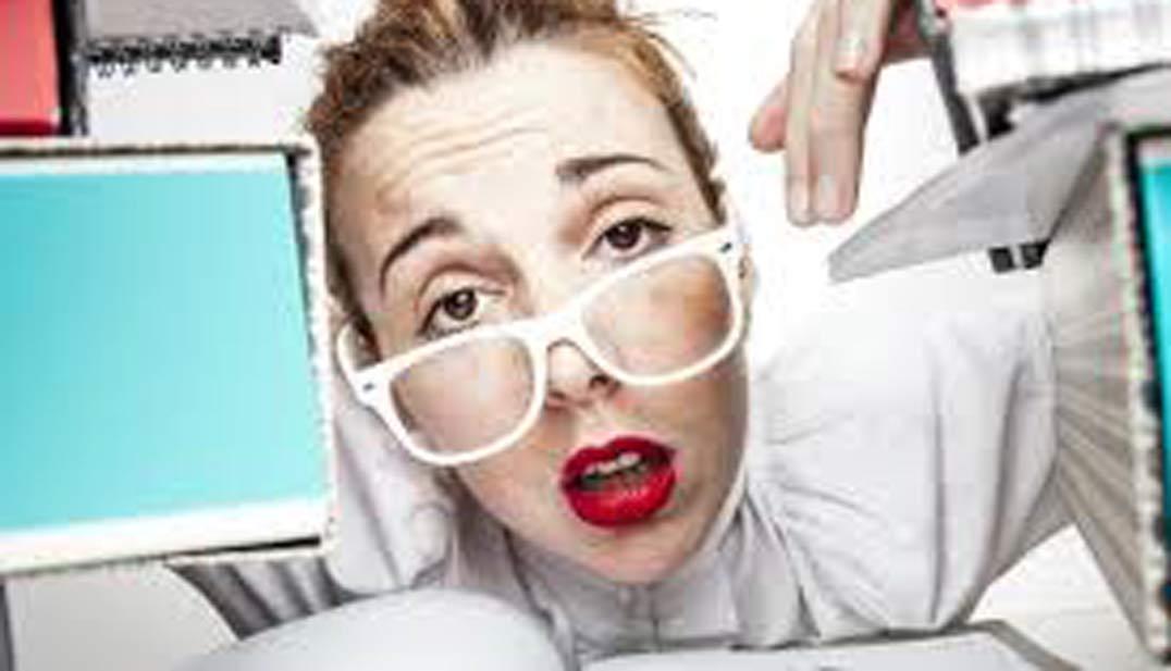 mujer con gafas de montura blanca y gesto cómico agobiada entre ordenadores y libros