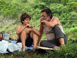 Hombre maduro, Portu, hablando con niño, Zezé, en el campo, sentados, para crítica de la novela mi planta de naranja lima, fotograma del filme
