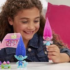 Niña jugando con muñecos trolls, anuncio comercial
