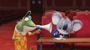 Camaleona vieja, hablando con un micro a mum el Koala en patio de butacas, personajes de Canta, película de dibujos