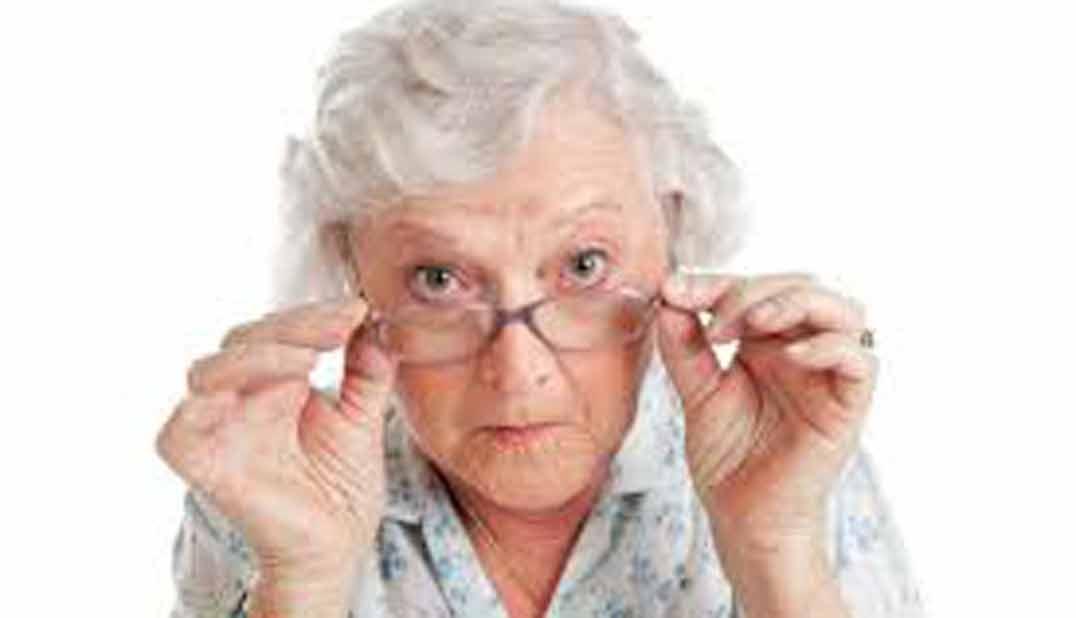 abuela tocándose con ambas manos las gafas observando a la cámara actitud crítica