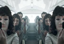 Imagen de personas con máscaras sentadas en un autobús mirando todos el móvil