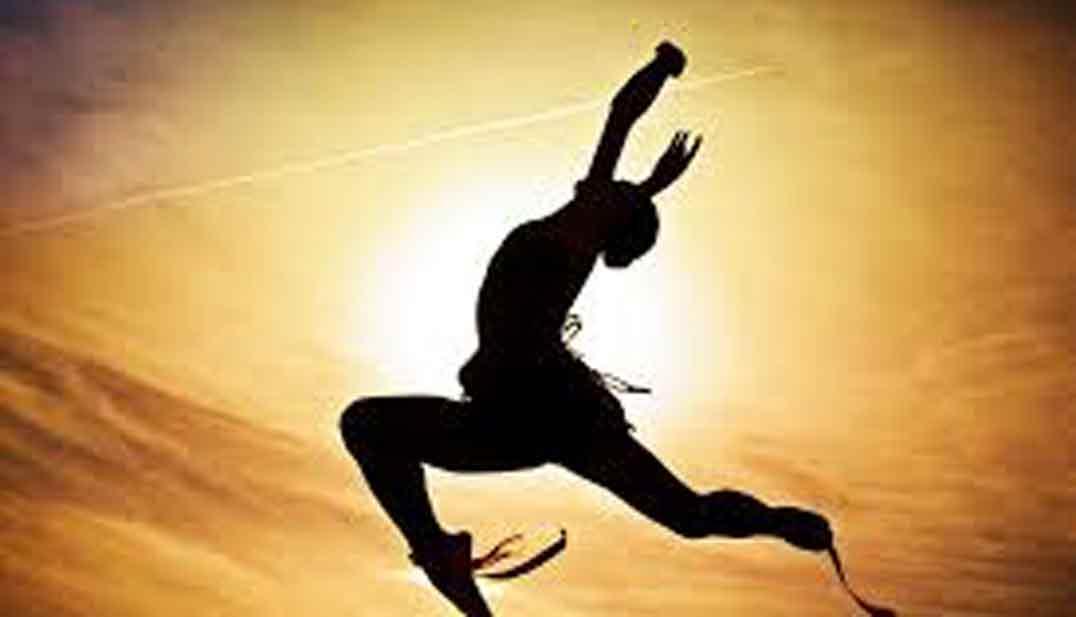 figura humana en sombra saltando con el sol detras y resplandores ocre, foto