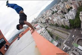 Hombre haciendo equilibrio sobre sus manos en el borde de una terraza
