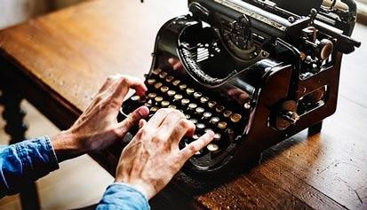 manos sobre maquina de escribir antigua